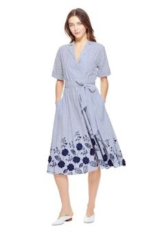 <ul><li>Short sleeve wrap dress with floral embroidered hem</li><li>Spread collar with v-neck and tie at natural waist</li><li>100% Cotton</li><li>Dry Clean Only</li></ul>
